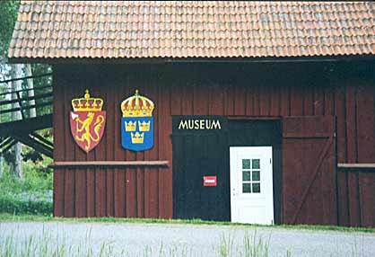 Fasad Norsk Veteranmuseum med Norges riksvapen och Sveriges lilla riksvapen